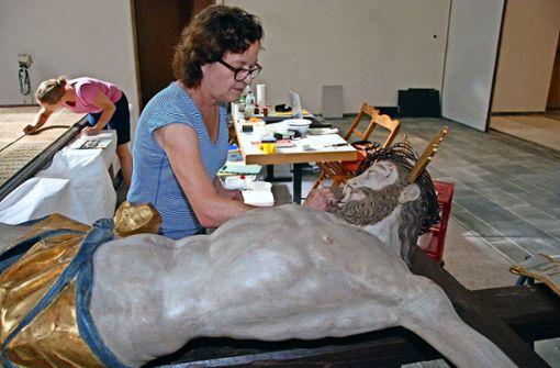 Caroline Walther behebt einige Schäden, die sich im Laufe der Jahre am großen Kruzifix ergeben haben. Foto: Kuhn