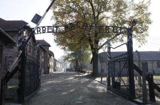 Männer und Frauen schlachten Ziege und entblößen sich vor ehemaligem KZ