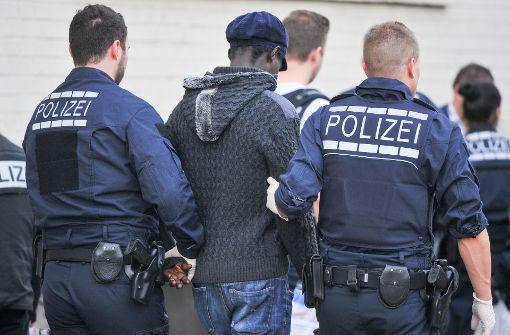 Ein Flüchtling wird bei einer Razzia abgeführt: Laut Innenministerium ist die Zahl der Straftaten in Asylunterkünften 2016 deutlich angestiegen. Foto: dpa
