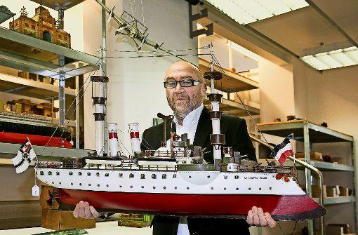 Erst versteigern, dann verpacken: Hans Georg Grupp (hier mit dem Märklin-Schlachtschiff Kaiser Wilhelm II.) hat auch nach der Auktion   alle Hände voll zu tun. Über ihm schwebt – eher unscheinbar – die Ju G38, die für 216 000 Euro den Besitzer gewechselt hat. Foto: Rudel
