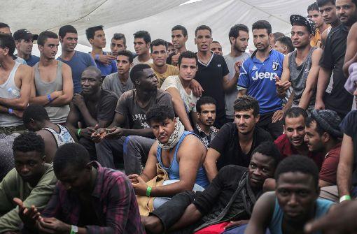 Flüchtlinge sitzen auf einem Rettungsschiff, nachdem sie vor der libyschen Küste gerettet wurden. Foto: AP