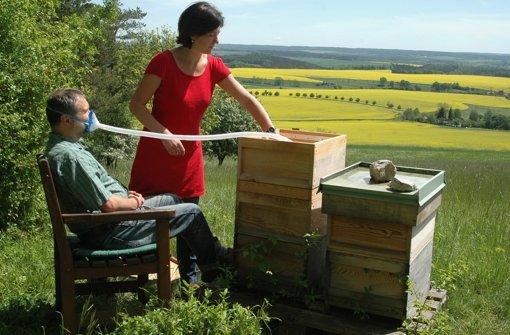 Die Heilpraktikerin Janett Conrad aus Jena lässt einen Patienten Luft aus einem Bienenstock inhalieren. Foto: dpa