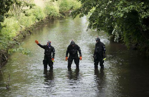 Ermittler suchen den Bachlauf des Mühlbachs in Offenburg ab. Foto: dpa
