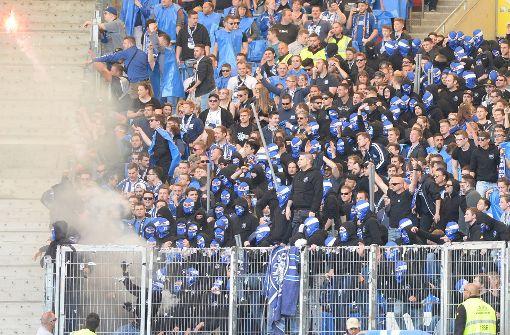 Vermummte Karlsruher Fans werfen Feuerwerkskörper in Richtung Spielfeld. Foto: dpa