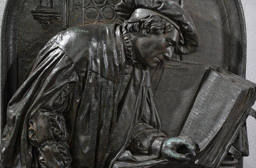Luther und  die Sprache: Ein Relief mit der Darstellung Martin Luthers als Bibelübersetzer auf der Wartburg Es gehört zum Sockel der Luther Plastik in Eisleben. Foto: dpa