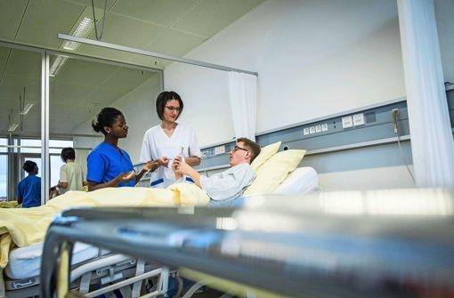 Die Pflegerinnen Olivia Appiah (links) und Jennifer Huber am Krankenbett. Foto: Lichtgut/Max Kovalenko