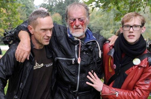 Zwei Männer stützen im Schlossgarten den verletzten Dietrich Wagner. Mittlerweile ist klar, dass der 66-jährige Renter nahezu blind bleiben wird. Foto: dpa