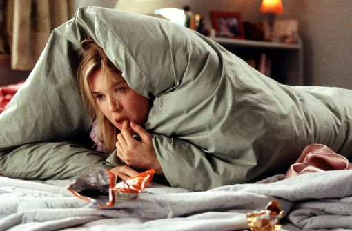 """Filmberühmter Liebeskummer in """"Bridget Jones – am Rande des Wahnsinns"""" : Bridget Jones (gespielt von Renée Zellweger) liegt frustriert in ihrem Bett und tröstet sich mit Süßigkeiten (Szenenfoto). Foto: UIP"""