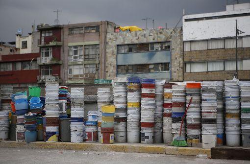 Plastik-Eimer, die zum Aufsammeln von Schutt benutzt wurden, stehen in Mexiko-Stadt aufeinander gestapelt an einer Straße. Foto: AP