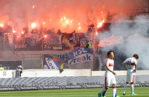 Anhänger des Karlsruher SC werfen massenweise Feuerwerkskörper beim Spiel gegen den VfB Stuttgart. Foto: Pressefoto Baumann