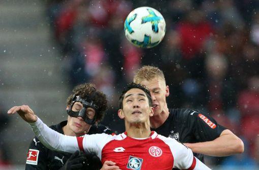 Die Stuttgarter Benjamin Pavard (links) und Timo Baumgartl (rechts) im Kampf um den Ball mit dem Mainzer Yoshinori Muto Foto: dpa