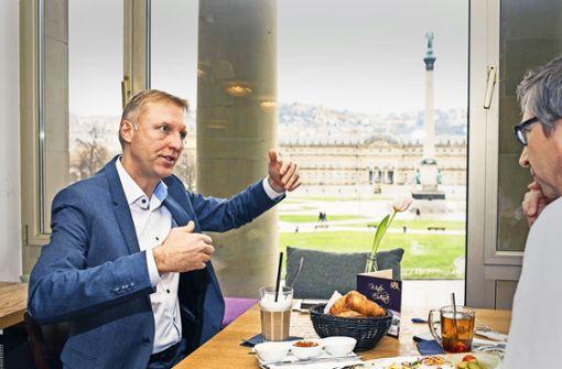 Armin Dellnitz im Gespräch mit Blick auf das Herz von Stuttgart – den Schlossplatz vom Café Königsbau aus gesehen. Foto: Lichtgut/Kovalenko