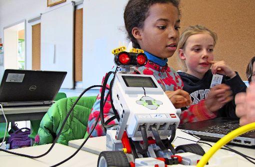 Junge Mädchen programmieren Legoroboter