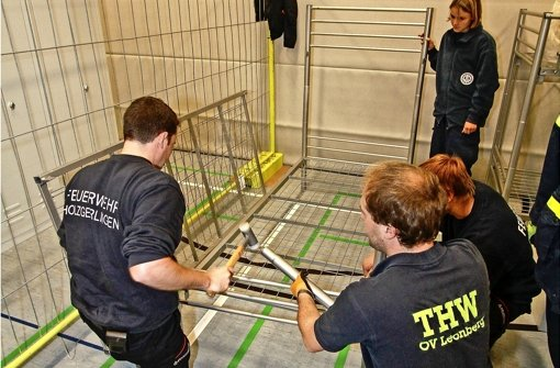 THW und Feuerwehr helfen beim Betten-Aufbau in der BSZ-Turnhalle. Foto: factum/Bach