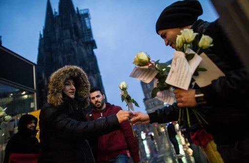 Versuch der Wiedergutmachung: Ein Mitglied eines deutsch-tunesischen Vereins verteilt in Köln Blumen an Passantinnen. Foto: dpa