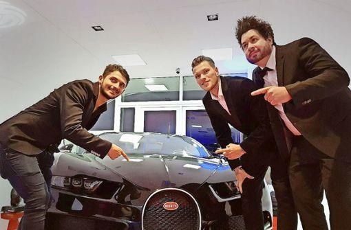 Die VfB-Profis Matthias Zimmermann (li.) und Daniel Ginczek (Mitte) mit Michael Konz vor dem 1500-PS-Bugatti im  futuristisch wirkenden Showroom. Foto: Klaus Schnaidt