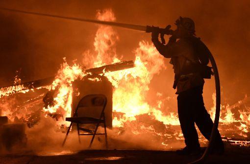Ein Feuerwehrmann bekämpft in Santa Paula ein Buschfeuer, das von heftigem Wind angefacht wird. Foto: dpa