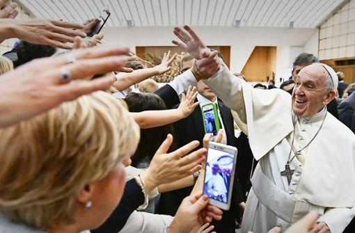 Papst Franziskus grüßt Gläubige, während er zu einer Audienz mit Angestellten aus dem Gesundheitswesen kommt Foto: dpa
