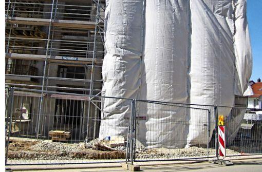 Hinter der Plane entstehen die neuen Balkone, davor liegen noch Trümmer. Foto: Bock
