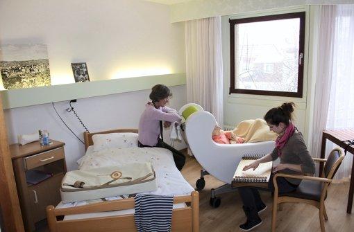Eva Trede-Kretschmar (links) am Bett ihrer Mutter. Musiktherapeutin Sandra Zeitler (rechts) spielt Monochord. Foto: Torsten Ströbele
