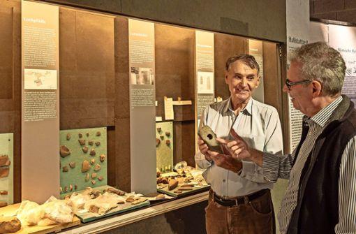 Besuch während des Ausstellungsaufbaus: Der Kurator Tiberius Bader erklärt ein Beil, das sich ein Steinzeitmensch als Werkzeug mühsam geschaffen hat. Foto: factum/Weise