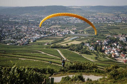 Andreas Koppenhöfer schwebt mit seinem gelben Schirm über die Weinberge hinab    an den Ortsrand von Korb. Foto: Gottfried Stoppel