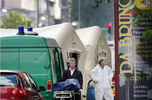 Mafiamord in Duisburg: Ein Bestatter schiebt 2007  eine Trage mit einer verdeckten Leiche von einem Tatort. Foto: dpa