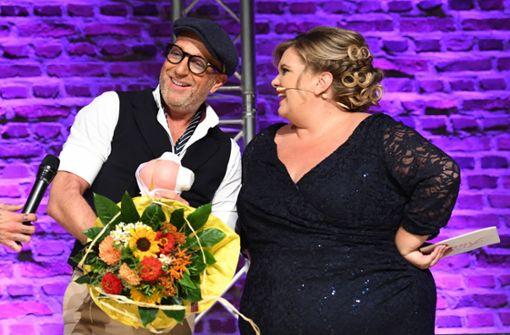 """Modedesigner Thomas Rath steht mit dem Veranstalterin Melanie Hauptmanns bei der bundesweiten Fashion-Gala """"Fräulein Kurvig"""" auf der Bühne. Foto: dpa"""