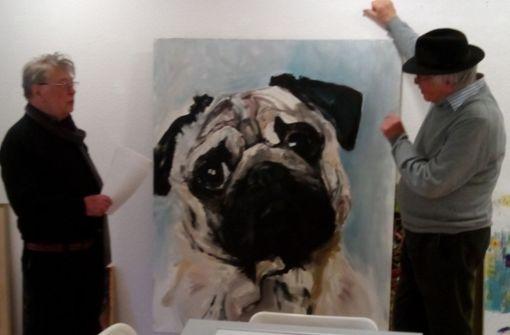 Klaus Bushoff, zweiter Vorsitzender des Vereins Inter Art, und der Künstler Günter  Guben (rechts) betrachten  in der Galerie an der Rosenstraße den Hundekopf, den die Künstlerin  Evelyn Schmidt gemalt hat. Foto: Cedric Rehman