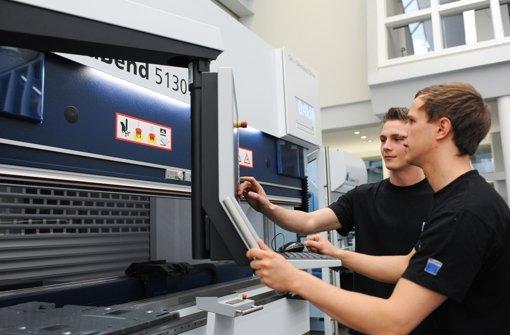 Jan Rauser (links) und Yannic Burde arbeiten bei Trumpf an einer Werkzeugmaschine Foto: Michele Danze