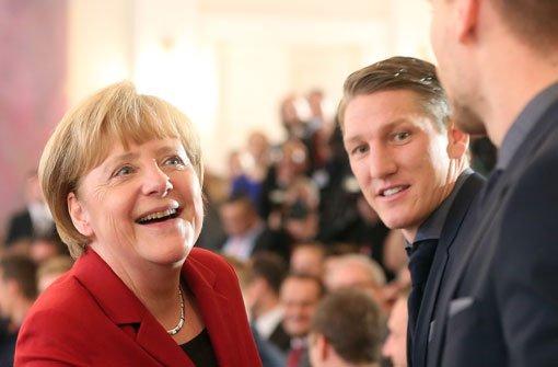 Bundeskanzlerin Angela Merkel und der Kapitän der deutschen Nationalmannschaft, Bastian Schweinsteiger. Foto: dpa