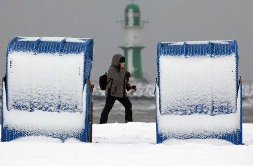 Am Ostseestrand von Warnemünde (Mecklenburg-Vorpommern) stehen am Mittwoch die Strandkörbe im Schnee. Starke Schneefälle sorgen auch für winterliches Flair an der Küste. Foto: dpa