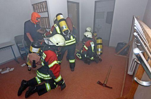 Beim simulierten Brandort wird ein Eingeschlossener gefunden: Die Hemminger Feuerwehr im Übungseinsatz im Keller der Gemeinschaftshalle. Foto: factum/Bach
