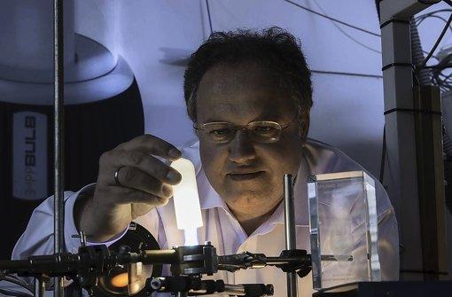 Mit einer Phosphorbeschichtung gelingt es Forscher Rainer Kling, die neu entwickelte Hochdrucklampe warm-weiß leuchten zu lassen. Foto: Martin Lober/KIT