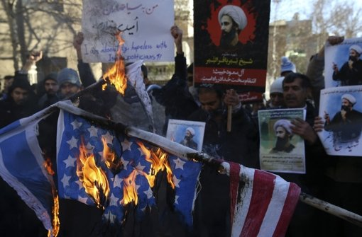Demonstranten im Iran brennen nach der Hinrichtung des schiitischen Geistlichen Nimr al-Nimr vor der Botschaft Saudi-Arabiens Flaggen nieder. Foto: AP