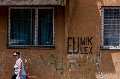 """Bei den Kosovaren ist """"Eulex"""" nicht beliebt – eine Frau vor einem Graffito in der Hauptstadt Pristina. Foto: AFP"""