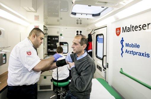 Khaled Shamsi misst den Blutdruck von Jamal Aldieen. Sowohl der Arzt als auch der Patient stammen aus Syrien – und treffen sich auf einem Parkplatz Foto: Lichtgut/Horst Rudel