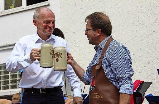Der Technische SWSG-Geschäftsführer Helmuth Caesar (li.) und Noch-Bezirksvorsteher Wolfgang Stierle  stoßen gemeinsam an – auch auf  den gelungenen  Marktplatz. Foto: Georg Friedel