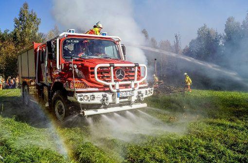Feuerwehrmänner löschenbei einer Katastrophenschutzübung ein Feuer. Als fiktiver Rahmen dieser Übung wird eine langanhaltende Hitzewelle angenommen. Foto: SDMG