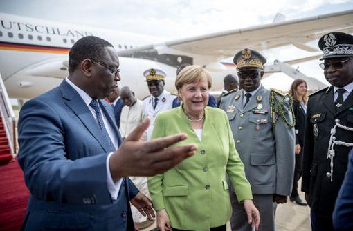 Bundeskanzlerin Angela Merkel (CDU) wird von Macky Sall, dem Präsidenten der Republik Senegal, am Flughafen begrüßt. Foto: dpa