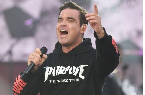 Robbie Williams unterschreibt auf blanken Brüsten