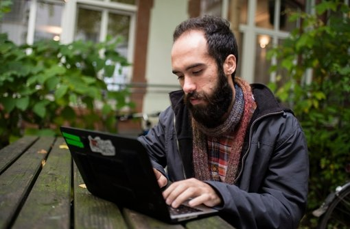 """Der syrische Flüchtling Hekmat Qassar arbeitet beim """"Refugee Hackathon"""" in Berlin an einem Laptop. Foto: dpa"""