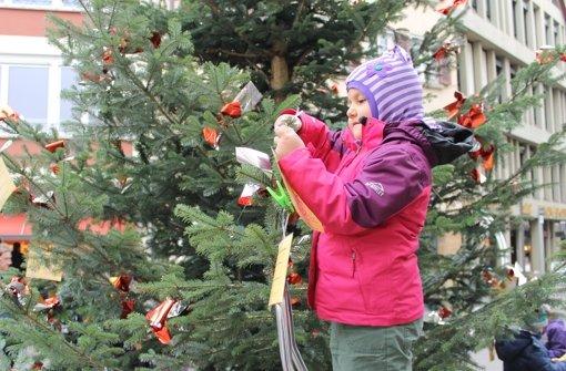 Die fünfjährige Cecilia hat dabei geholfen, die Wunschzettel an den Baum vor der Stadtkirche zu hängen. Foto: Maira Schmidt