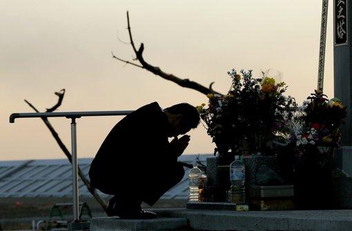 Viele beten an den Schreinen, legen Blumen nieder oder zünden Kerzen für die Opfer an. Foto: EPA