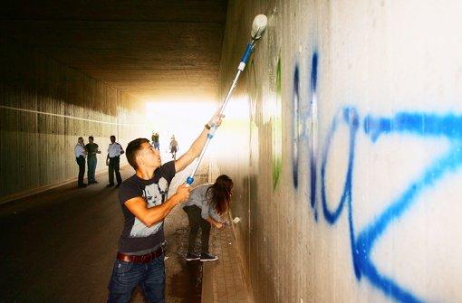 Jugendliche übermalen obszöne Graffiti