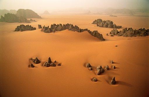 Zwischen den bizarren Gesteinsformationen im oxidierenden Sand der Wüste des Nord-Tschad zieht gerade ein Sandsturm auf  Foto: © George Steinmetz
