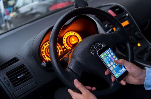 Nur ein kurzer Blick – das Handy-Verbot am Steuer wird häufig missachtet. Foto: dpa