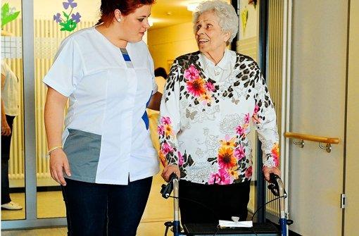 Ana Carina Dias aus Aveiro in Portugal (li.) begleitet im Alten- und Pflegeheim Karl Wacker in Stuttgart Bewohnerin Helga Kast mit Rollator durch einen Flur. Foto: dapd