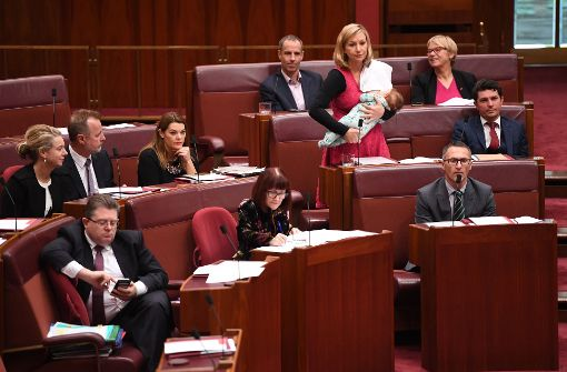 Abgeordnete hält Rede und stillt dabei