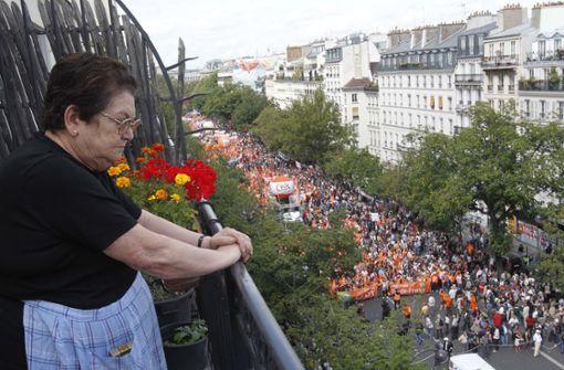 Eine Frau beobachtet aus sicherer Entfernung den Protest gegen die Regierung Paris.  Foto: AP